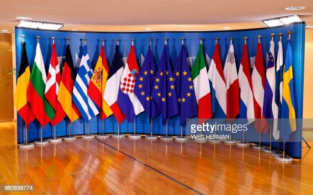 Flags of 16 EU countries are seen ahead of an emergency European Union leaders at EU headquarters in Brussels on June 24 2018 EU leaders headed to...