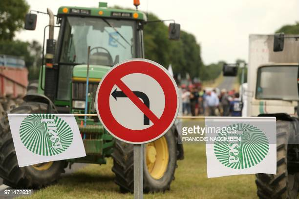 Flags of French FNSEA farmers' union hang on a road sign as farmers block access to the Vatry refinery on June 11, 2018 in the French department of...