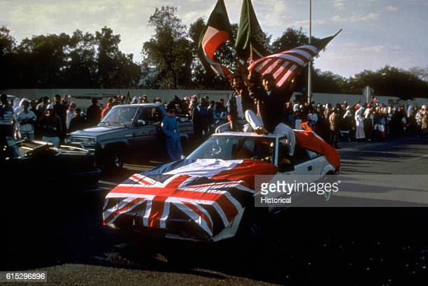 Flags of nations in the Coalition are displayed on a car in a parade celebrating the liberation of Kuwait from Iraqi occupation during Operation...