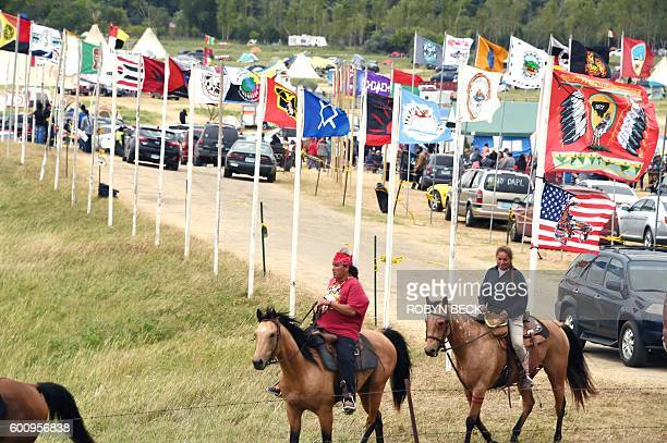 Flags of Native American tribes from across the US and Canada line the entrance to a protest encampment near Cannon Ball, North Dakota where members...