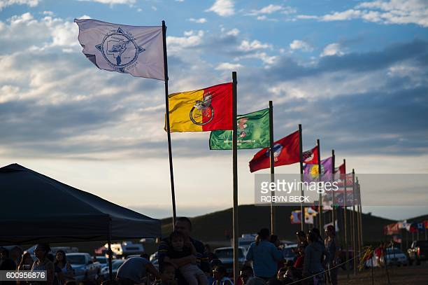 Flags of Native American tribes from across the US and Canada line the entrance to a protest encampment near Cannon Ball North Dakota where members...