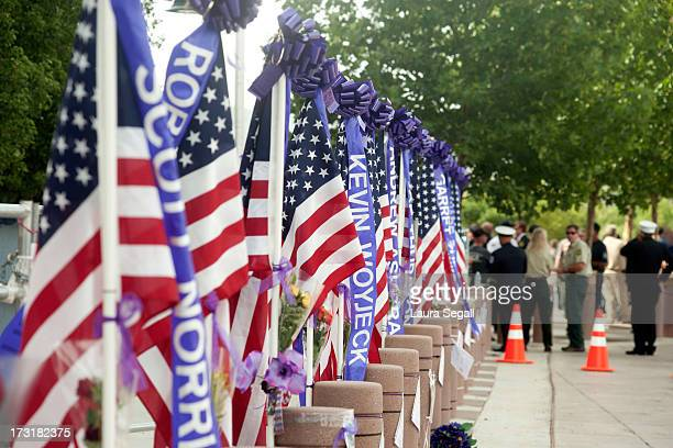 Flags of the 19 firefighters killed in a wildfire line the entrance to a memorial service in their honor at Tim's Toyota Center July 9 2013 in...