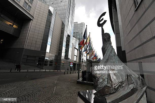 Flags of the EU member states fly near a statue holding the euro sign in front of the European Parliament in Brussels on July 19 2012 Eurozone...