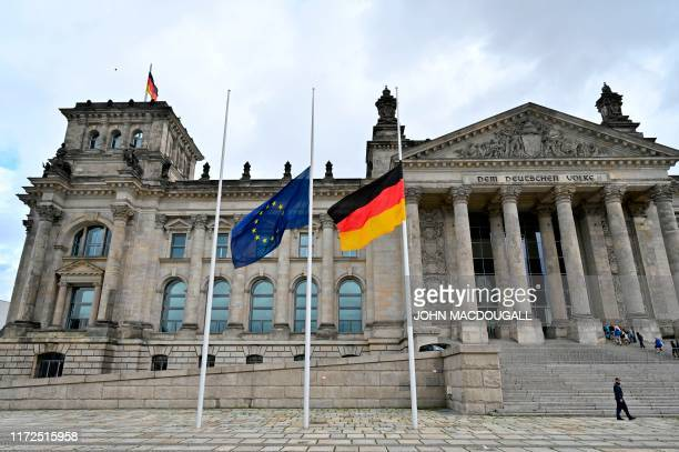 Flags of the European Union and of Germany fly at halfmast in front of the Reichtag building housing the Bundestag in Berlin on September 30 in a...