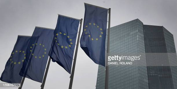 Flags of the European Union flutter in front of the headquarters of the European Central Bank in Frankfurt am Main western Germany on March 12 2020...