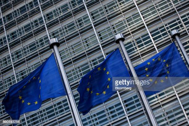 Flags of the European Union fly outside the Berlaymont building ahead of a news conference at the end of the fifth round of Brexit negotiations in...