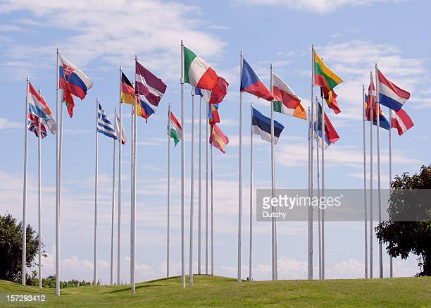 flags of the european union, in a circle, on tall flagpoles  - european union stock pictures, royalty-free photos & images