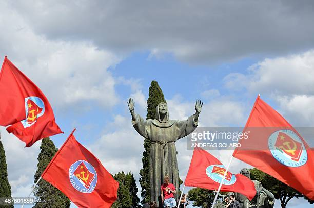 Flags of the former Italian Communists party fly next to a statue of St Francis of Assisi during the workers' day concert which celebrates Mayday in...