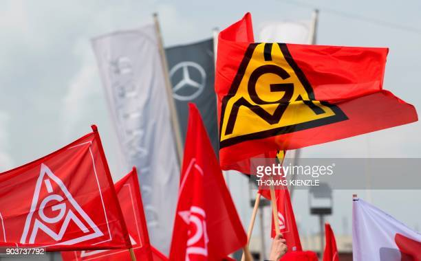 Flags of the German metalworkers' union IG Metall wave in front of the plant of EvoBus a subsidiary company of Daimler AG during a warning strike in...