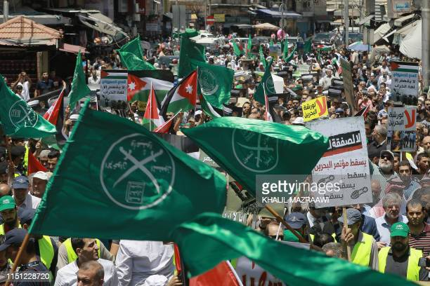 Flags of the Muslim Brotherhood, Jordan, and other political parties are waved with other protest signs denouncing the US-led Middle East economic...