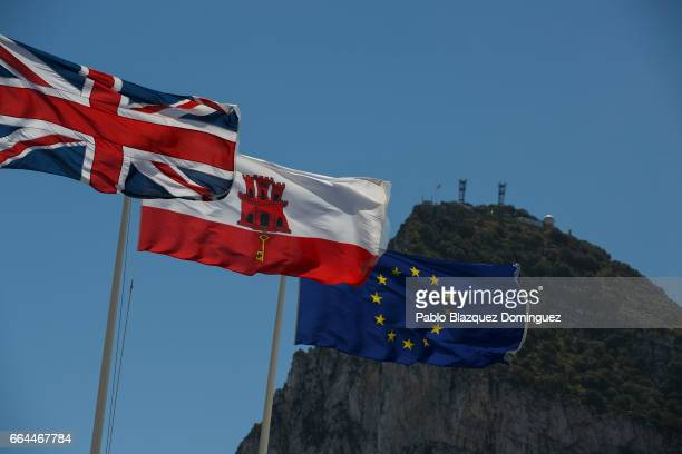 Flags of the United Kingdom Gibraltar and the European Union are flown while the Gibraltar Rock is seen on the back at the SpainGibraltar border on...