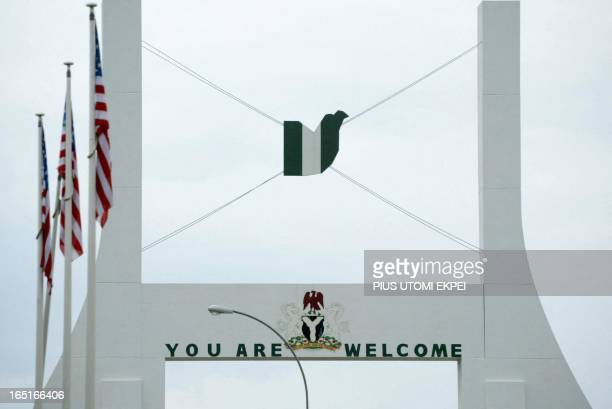Flags of the United States of America are displayed at the Abuja city gate 10 July 2003 ahead of United States President George W Bush's visit to...
