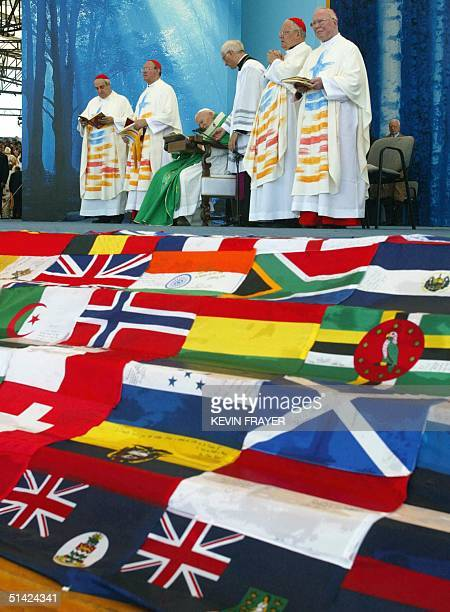 Flags of the world adorn the stage as Pope John Paul II reads during the World Youth Day papal mass of World Youth Day at Downsview Park in Toronto...