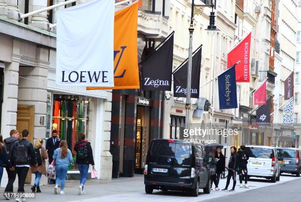 Flags of various brands and logos line the streets in the Luxury Fashion and Jewellery shopping area on London's New Bond Street