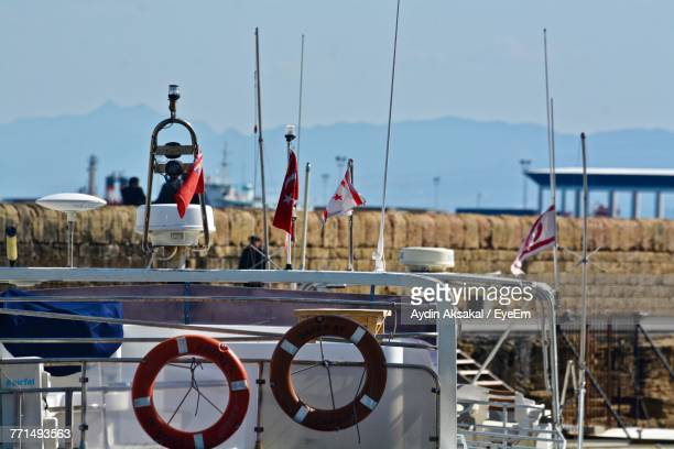 Flags On Boat Against Sky