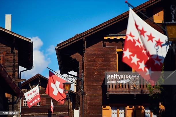 Flags on chalet buildings, Valais, Switzerland