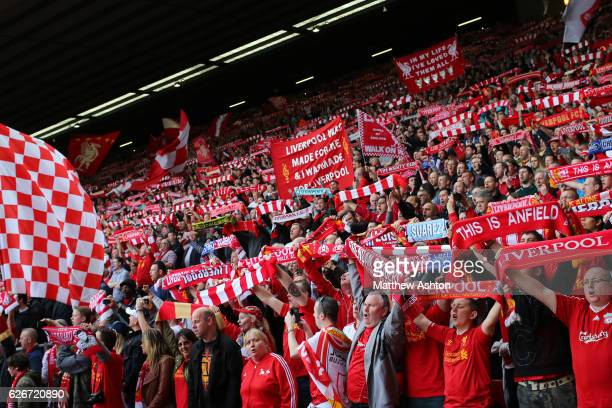 Flags on The Kop at Anfield home stadium of Liverpool as fans sing YOU'LL NEVER WALK ALONE and hold up their scarfs