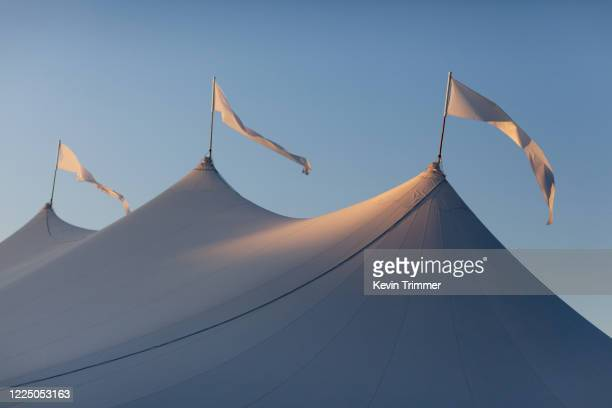 flags on-top of large event tent during sunset - entertainment tent stock pictures, royalty-free photos & images