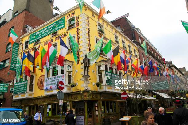 Flags outside colorful yellow Oliver St John Gogarty pub in Temple Bar area Dublin city center Ireland Republic of Ireland