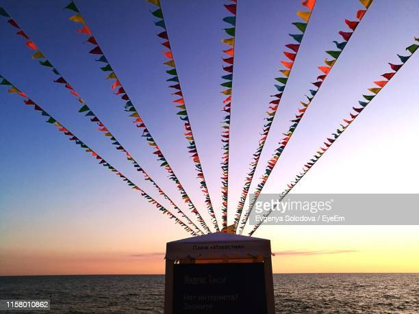 flags over tent at beach against sky during sunset - sochi stock pictures, royalty-free photos & images
