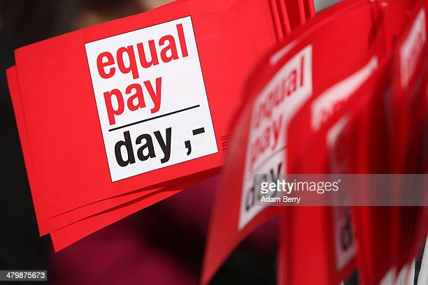 Flags reading 'Equal Pay Day' are seen during the 'Equal Pay Day' demonstration on March 21, 2014 in Berlin, Germany. The annual event recognizes the...