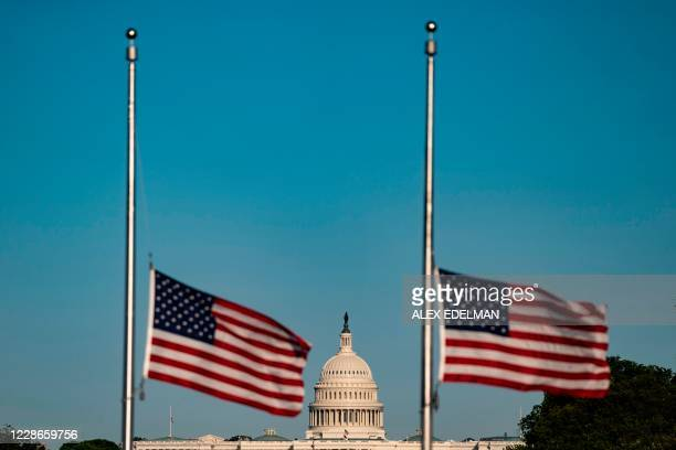 Flags sit at half-staff the evening before a memorial service for late US Supreme Court Justice Ruth Bader Ginsburg at the US Supreme Court on...