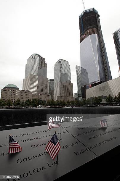 S flags stand among a list of victims' names on a memorial pool during tenth anniversary ceremonies of the September 11 2001 terrorist attacks at the...