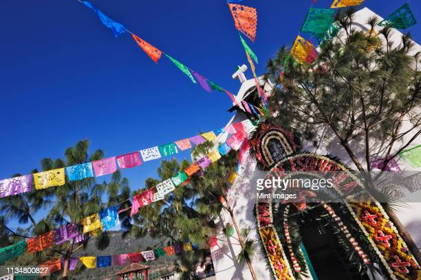 flags streaming from chapel - chiapas stock pictures, royalty-free photos & images