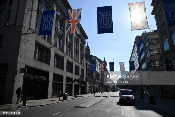 Flags thanking key workers efforts during the coronavirus crisis fly above Oxford Street in London on June 16, 2020. - Various stores and outdoor...