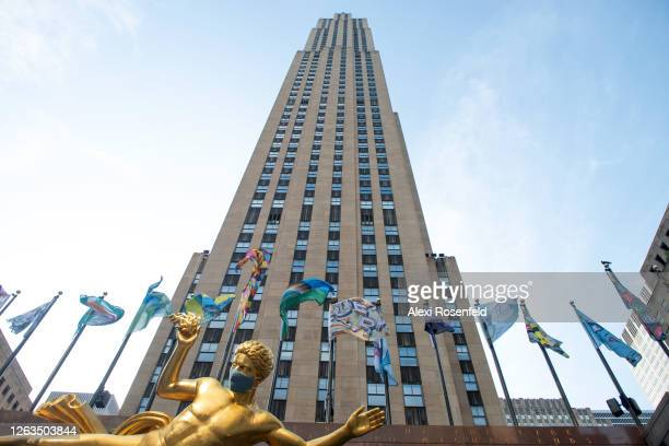 """Flags that are part of """"The Flag Project"""" are seen flying behind Paul Manship's 'Prometheus' statue wearing a mask with a view of the 30 Rockefeller..."""