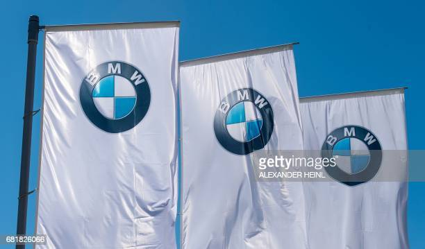 Flags with the BMW logo are pictured prior to the annual general meeting in Munich on May 11 2017 / AFP PHOTO / dpa / Alexander Heinl / Germany OUT