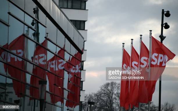 Flags with the logo of Germany's social democratic SPD party reflect in a facade at the venue of an extraordinary SPD party congress in Bonn western...
