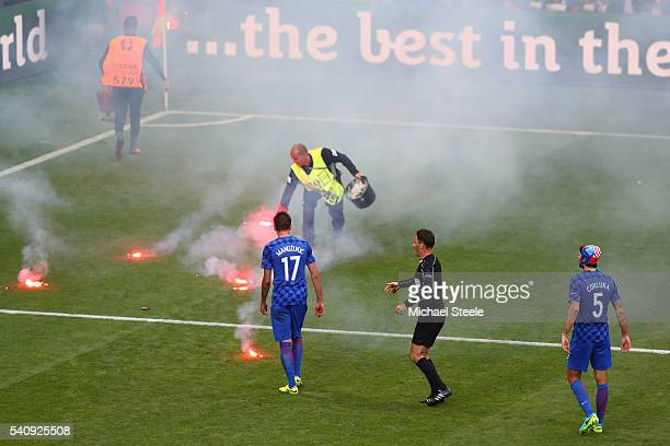 Flairs are thrown onto the pitch during the UEFA EURO 2016 Group D match between Czech Republic and Croatia at Stade Geoffroy-Guichard on June 17,...