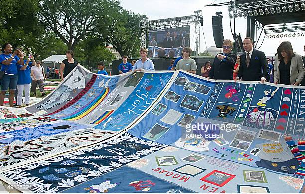 Flamboyant British pop icon Elton John helps to unfold a panel of the AIDS Quilt on the National Mall July 23 2012 as part of the 19th International...