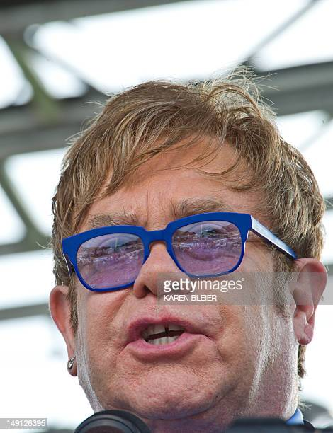 Flamboyant British pop icon Elton John reads names appearing on the AIDS Quilt on the National Mall July 23 2012 as part of the 19th International...
