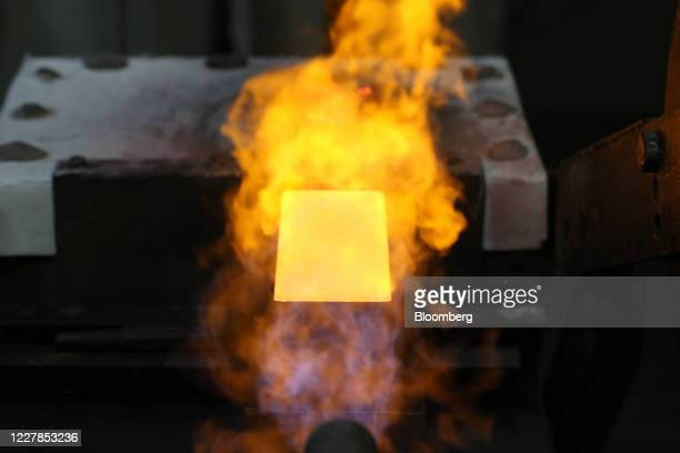 Flame alights a newly-poured gold ingot in its mold at the Uralelectromed Copper Refinery, operated by Ural Mining and Metallurgical Co. , in...