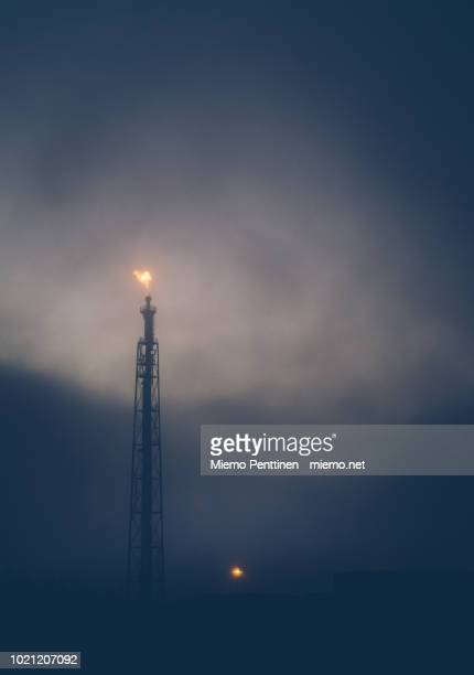 flame burning at an oil refinery exhaust tower on a cloudy night - flare stack stock photos and pictures