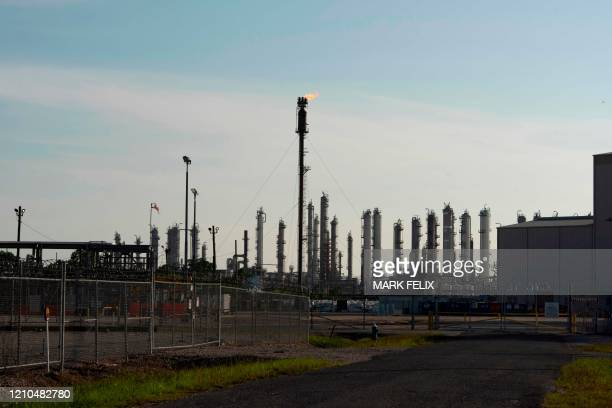 Flame burns at the top of petrochemical plant in Houston, Texas, on April 20, 2020. - US oil prices rebounded back above zero on April 21, a day...