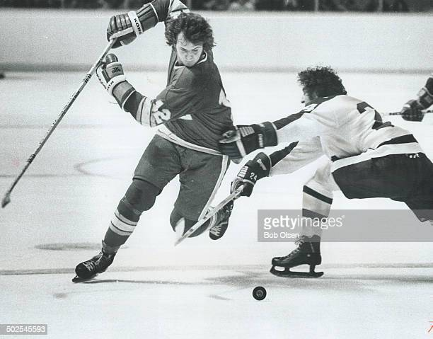 Brian Glennie Maple Leaf defenceman uses outstretched arm and stick to shop the forward progress of Atlanta Flames' Tom Lysiak during National Hockey...