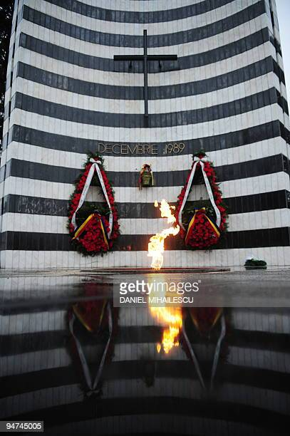 A flame is reflected in front of the monument of The Revolution's Heroes in Timisoara city on December 12 2009 Romania is marking the 20th...