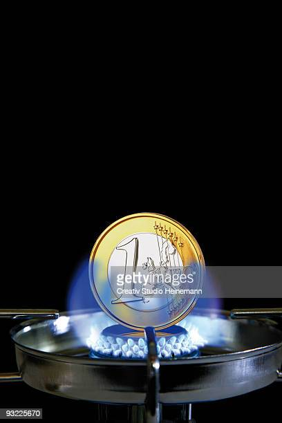 One euro coin on gas stove flame, close-up (digital composite)