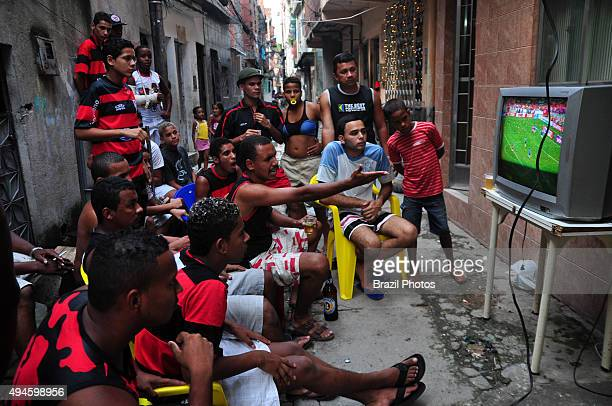 Flamego fans watch soccer game on TV in a Favela da Mare alley Rio de Janeiro Brazil Flamengo is the most popular team in Brazil and one of the most...