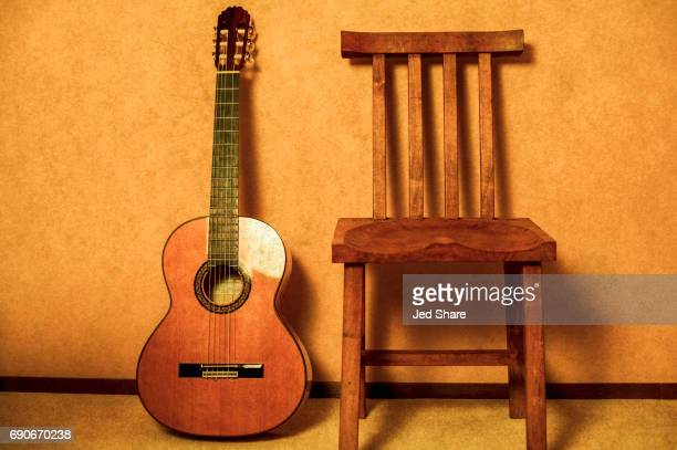 flamenco classical guitar and a chair to sit & play - classical guitar stock photos and pictures