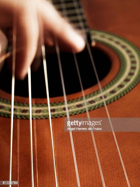 A flamenco guitarist playing guitar in Spain. 2008. Selective focus on the strings.