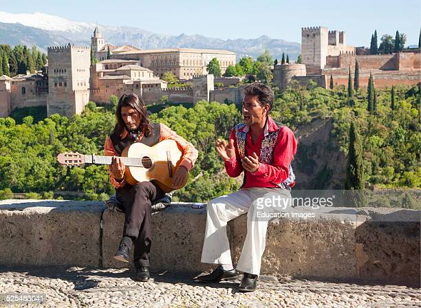 Flamenco musicians play with a backdrop of the snow Sierra Nevada mountains and the Alhambra Granada Spain
