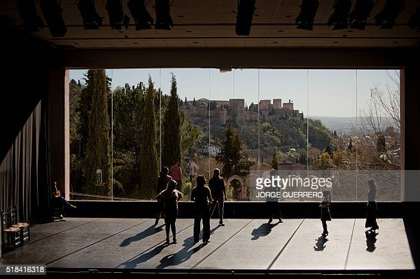 Flamenco students dance at the 'International School of Flamenco Manolete' with the Alhambra in background in Granada on March 29 2016 / AFP / JORGE...