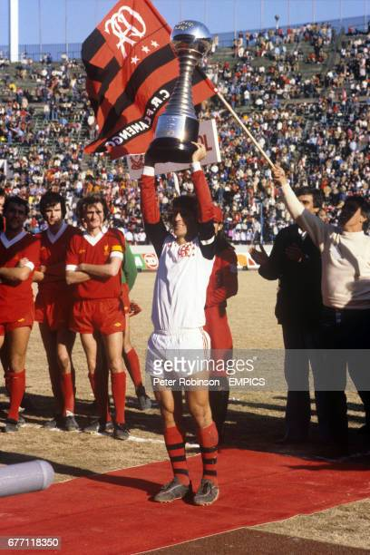Flamengo captain Zico holds up the Tokyo Cup as Liverpool's Ray Kennedy Alan Hansen and Phil Thompson look on