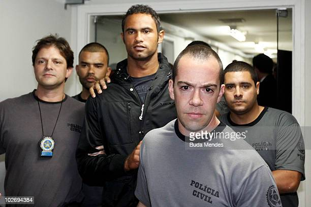 Flamengo goalkeeper Bruno Fernandes is guarded by officers as he turns himself in to the police at the Polinter station of Andarai Neighborhood on...