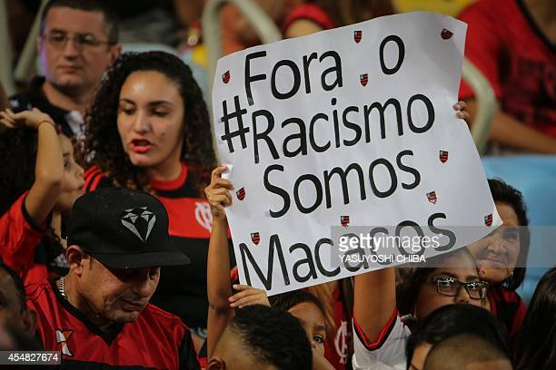 Flamengo's fans hold a sign against racism before their Brazilian championship match against Gremio at Maracana stadium in Rio de Janeiro Brazil on...