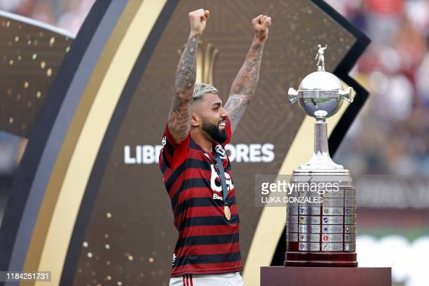 TOPSHOT Flamengo's Gabriel Barbosa celebrates next to the trophy after winning the Copa Libertadores final football match by defeating Argentina's...